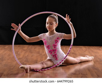 Rhythmic gymnastic girl and ring on black background.