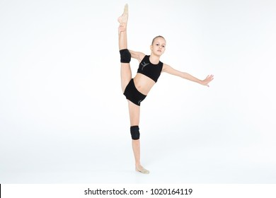 Rhythmic gymnastics caucasian blonde girl in black suite performing athelete exercises showing flexibility and acrobat balance on white background isolated