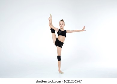 Rhythmic gymnastics caucasian blonde girl in black suite performing athelete exercises showing flexibility and stretching abilities acrobat balance on white background isolated