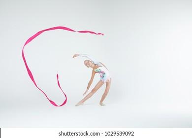 Rhythmic gymnastics caucasian blonde girl in sportswear dress showing flexibility and acrobat balance on white background isolated