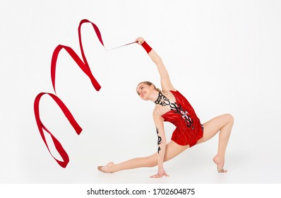 Rhythmic gymnastics. Professional sportswoman with red string dancing in leotard, isolated on white