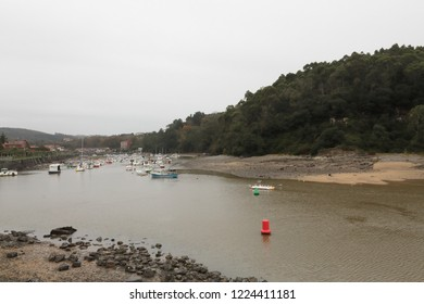 The ria hore of Plentzia, in the Basque Country, Spain, during a cold cloudy winter day, with low tide and small private boats on the mud