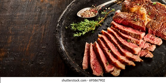 Rib eye steak cut in slices served on plate with spoon full of spices