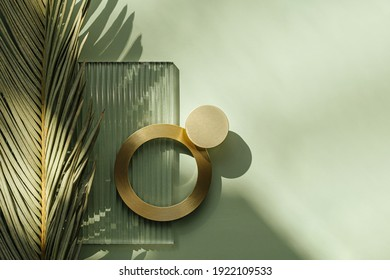 Ribbed acrylic plate and  golden ring on green background with tropical leaf and shadow. Natural and manmade materials mixture.