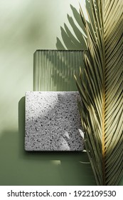 Ribbed acrylic plate and square stone plate on green background with tropical leaf and shadow. Natural and manmade materials mixture.  Stylish background for presentation.