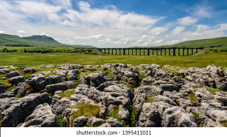 Ribblehead, England, UK - July 3, 2015: A train of freight containers crosses the Ribblehead Viaduct on the scenic Settle and Carlisle railway in England's Yorkshire Dales National Park.