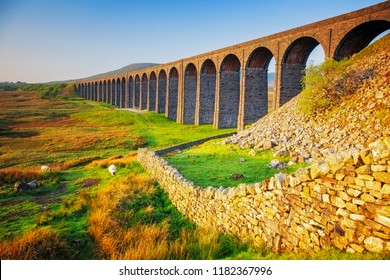 Ribblehead Viaduct with rocks in foreground in Yorkshire Dales in UK.