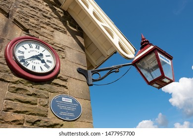 Ribbleshead, North Yorks, UK - Circa August 2019: Ornate railway station clock and lantern seen on a station on the famous Leeds to Carlisle railway route. A blue plaque is also mounted on the wall.