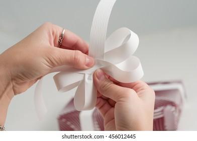 Ribbon bow gift box handmade craft hand fold stripe decoration manual directions isolated