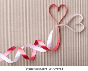 Ribbon hearts like interwoven snakes on beige paper background
