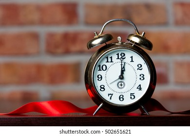 Ribbon and little alarm clock on brick wall background