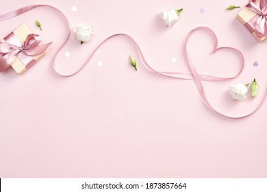 Ribbon in shape of heart with gift boxes and rose flowers on pink background. Happy Valentines day, Mothers day, birthday concept. Romantic flat lay composition.  - Shutterstock ID 1873857664
