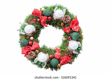 with ribbons, baubles and candles decorated evergreen yew wreath for christmas, on white background
