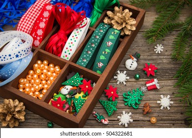 Ribbons, beads, toys, Christmas crafts in a wooden box.