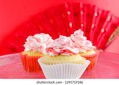 Ribbons of red and white frosting decorate fluffy, lemon vanilla cupcakes on red background