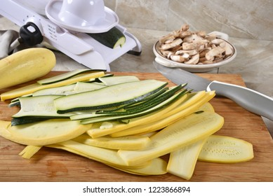 Ribbons of thin sliced zucchini and yellow squash on a cutting board with a mandolline slicer