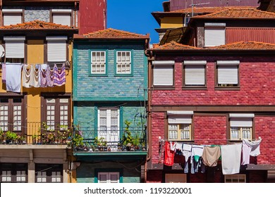 Ribeira District of Porto or Oporto city, Portugal. Typical colorful buildings, with clothes hanging in clothesline drying at sun and flower vases in balcony