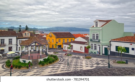 RIBEIRA GRANDE, AZORES, PORTUGAL - JUNE 29, 2017: Colored houses and ripple of pavement mosaic in the center of Ribeira Grande town, located on Sao Miguel island of Azores, Portugal.