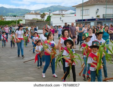 RIBEIRA GRANDE, AZORES, PORTUGAL - JUNE 29, 2017: Children at traditional cavalcade on central street of Ribeira Grande town, as secular part of yearly festivities on Day of St. Peter.