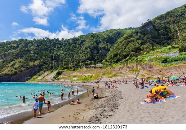 Ribeira Quente, Sao Miguel island, Azores, Portugal - August 15, 2020: People swimming in the sea and relaxing on a nice sandy beach Praia do Fogo by the town Ribeira Quente.
