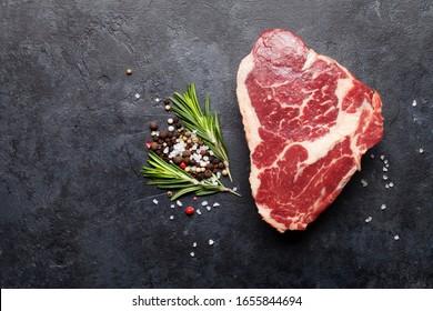 Ribeye frisches rohe Rindfleisch Steak mit Gewürzen auf Steinbrett. Draufsicht, flacher Laibe mit Kopienraum
