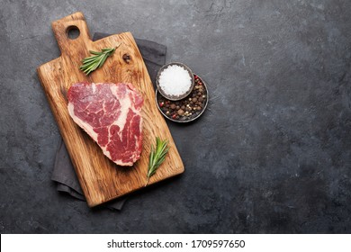 Ribeye fresh raw beef steak with spices on cutting board. Top view flat lay with copy space