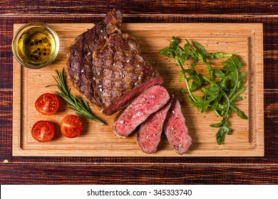 Ribeye steak with arugula and tomatoes on dark wooden background.