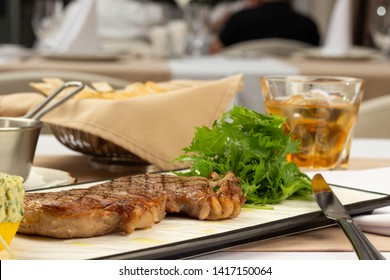 Ribeye steak with butter on a plate and a glass of whiskey.