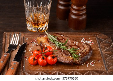 Ribeye steak with cherry tomatoes and rosemary on a wooden serving board. Flatware, a glass of whiskey, pepper mills. Restaurant food.