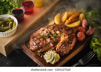 Ribeye steak with potatoes, onions and baked cherry tomatoes. Juicy steak with flavored butter.