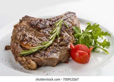 Ribeye Steak with rosemary. On a white plate