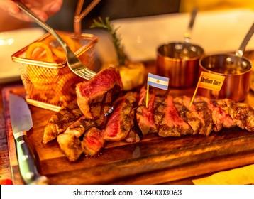 Ribeye and Striploin Steak on wooden plate .