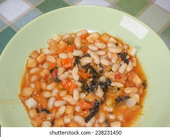 Ribollita meaning reboiled is a Tuscan soup made with bread and vegetables including leftover bread, cannellini beans, carrot, cabbage, beans, silverbeet, kale, and onion