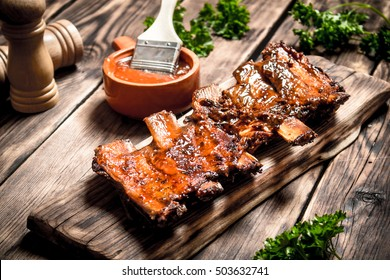 Ribs grill with beer and herbs. On a wooden table.