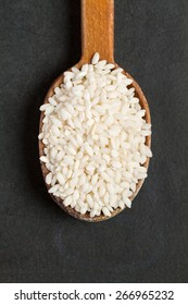 Rice Arborio in an old wooden spoon on a black background