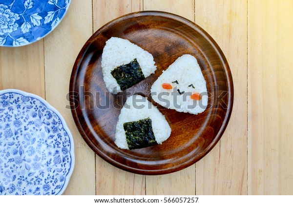 Rice ball (onigiri) on wooden background, selective focus with lens flare