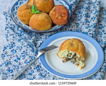 RICE BALLS SICILIAN STREET FOOD MADE OF RICE. Gluten Free Arancini with wild mushrooms and cream sauce on a wooden background with a floral fabric. Fast food, dinner. Close up