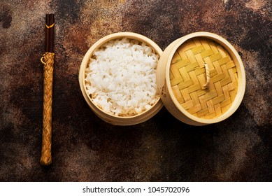 Rice in bamboo steamer with chopsticks on a brown concrete background, top view