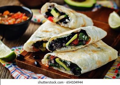 Rice black bean avocado tomato burritos. toning. selective focus