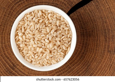 Rice in a bowl. Bowl with brown rice on a wooden round slices of oak, cutting board, top view.