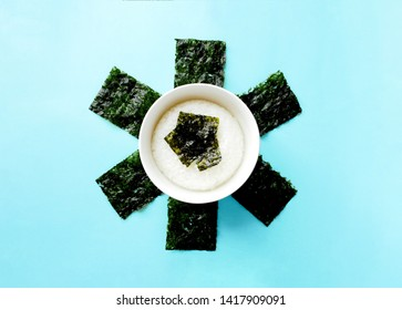 Rice bowl with Crispy Nori Seaweed on Blue background.Top view. Roasted sheets of seaweed.Asian healthy dry nori snack food.