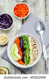 Rice bowl with red cabbage, carrots, avocado, arugula and hummus. toning. selective focus