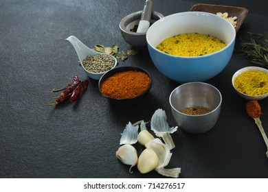Rice in bowl with various spices ingredients on black background