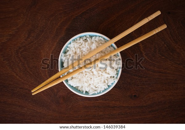 rice in a bowl and wooden chopsticks - isolated on wooden background