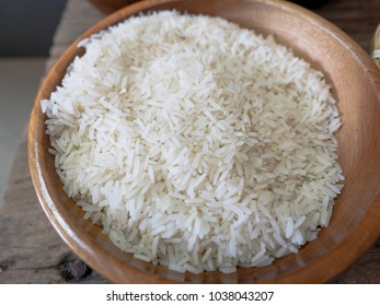 Rice bowl in a wooden bowl placed on a wooden background.