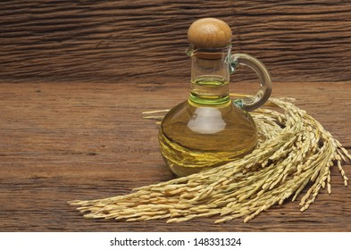 Rice bran oil in bottle glass with seed on the old plank wood