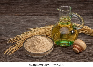 Rice bran oil in bottle glass with seed and bran on the old plank wood