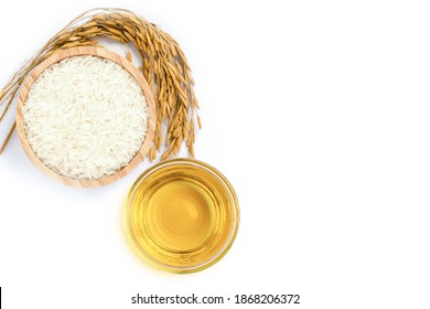 Rice bran oil extract with paddy and white rice on white background. Top view. Flat lay.