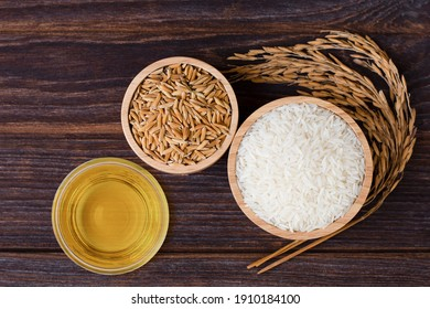 Rice bran oil extract with paddy and white jasmine rice isolated on wooden table background. Top view. Flat lay.