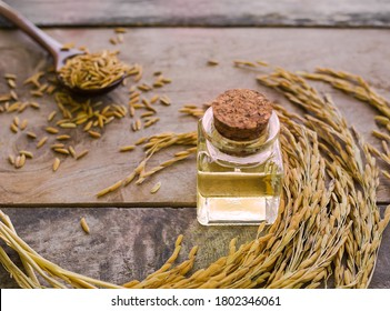 Rice bran oil in glass bottle with blur image of ear of rice on wood background. organic rice. thai food for healt concept.